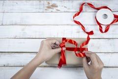 礼品包装材料,妇女组装礼物盒逐步与红色ribbo 免版税库存照片