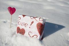 礼品和在雪的心形的棒棒糖 免版税图库摄影