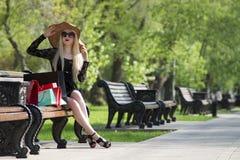 黑礼服、太阳镜和帽子的美丽的年轻时髦的白肤金发的妇女有购物袋的坐一条长凳在公园 免版税库存照片