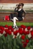 黑礼服、太阳镜和帽子的美丽的年轻时髦的白肤金发的妇女有购物袋的坐一条长凳在公园 免版税库存图片