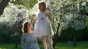 礼服亲吻母亲立场的可爱的女孩在摇摆在开花庭院里 t 股票录像