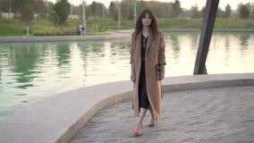 礼服和外套的美丽的浅黑肤色的男人走在池塘附近的在秋天公园 影视素材