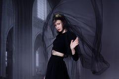 黑礼服和黑暗的面纱的美丽的女孩 免版税图库摄影