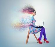 礼服和玻璃的女孩坐与膝上型计算机的一把椅子 免版税库存图片