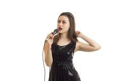 黑礼服唱歌歌曲的可爱的少妇与卡拉OK演唱 免版税库存照片