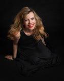 黑礼服摆在的美丽的淫荡妇女 免版税图库摄影
