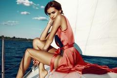 礼服构成夏天旅行游艇的美丽的性感的深色的女孩 库存照片