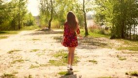 礼服步行的怀孕的女孩通过木头 股票录像