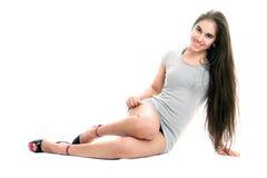 礼服灰色俏丽的微笑的妇女年轻人 免版税库存照片