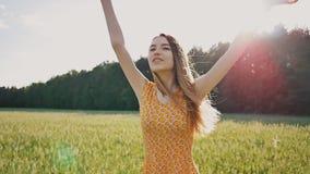 礼服的一个美丽的年轻俄国女孩通过麦田迅速跑 在森林附近长的头发飞行  股票录像