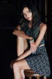 礼服的一个迷人的女孩坐在咖啡馆的一把木椅子 可能 图库摄影