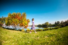 礼服的一名妇女在草走 免版税库存照片