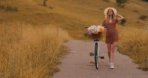 礼服的中间计划女孩去与自行车和花在领域 股票录像