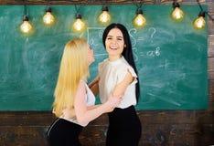 礼服的在愉快的面孔,在背景的黑板夫人 通过检查概念 有吸引力的学生congrats其中每一 库存照片
