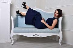 礼服的女孩在一个蓝色沙发说谎 免版税图库摄影