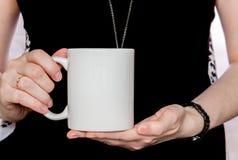 黑礼服的女孩在手上拿着白色杯子 免版税库存图片
