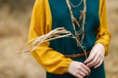 黄绿礼服的女孩在手上的拿着一棵草 图库摄影