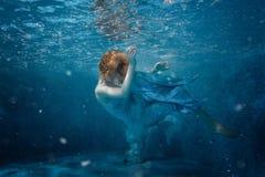 礼服的女孩在水池的底部 免版税库存图片
