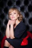 黑礼服的女孩坐一把红色椅子 图库摄影