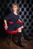 黑礼服的女孩坐一把红色椅子 免版税库存照片