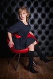 黑礼服的女孩坐一把红色椅子 库存照片