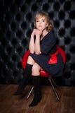 黑礼服的女孩坐一把红色椅子 库存图片