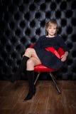 黑礼服的女孩坐一把红色椅子 免版税图库摄影