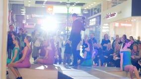 礼服的女孩坐阶段,无尾礼服的人用水在指挥台的,在狭小通道的时装表演女孩附近去, 股票录像