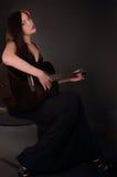 黑礼服的女孩弹吉他 免版税库存图片