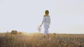 礼服的女孩有帽子的沿秸杆领域走 一件蓝色礼服的一名妇女是在与秸杆大包的领域 贴现女孩桃红色购物口气 股票视频