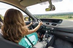 礼服的女孩有驾驶汽车的红色头发的 查出的背面图白色 免版税库存照片