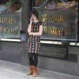 黑礼服的女孩有从五颜六色的微笑的印刷品的由电话讲话在客栈附近 免版税库存图片