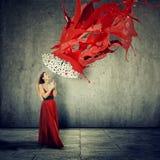 礼服的妇女使用作为风雨棚的一把伞反对RED丢弃绘跌倒 免版税库存图片