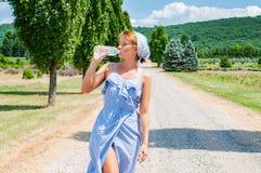 礼服的妇女在乡下走路 库存图片