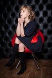 黑礼服的妇女坐一把红色椅子 库存照片