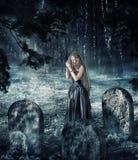 黑礼服的妇女祈祷在公墓的 免版税库存图片