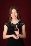 礼服的小姐用酒 关闭 深红的背景 免版税库存图片