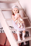 礼服的小逗人喜爱的白肤金发的女孩坐有如此的木台阶 库存图片