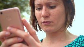 礼服的年轻俏丽的妇女使用坐在沿海岸区的智能手机在城市 股票视频