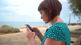 礼服的年轻俏丽的妇女使用坐在沿海岸区的智能手机在城市 影视素材