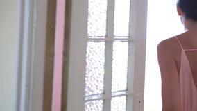 礼服的年轻可爱的妇女在公寓的老阳台在哈瓦那 股票录像