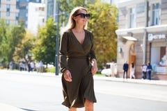 礼服的年轻白肤金发的妇女走在夏天街道的 库存照片