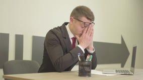 礼服的年轻紧张的被注重的坐在摩擦他的面孔的膝上型计算机前面的办公室的大忙人和玻璃 影视素材