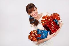 礼服的微笑的妇女拿着有礼品的三个配件箱 免版税库存图片