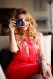 礼服的微笑的妇女有减速火箭的照相机的,在长沙发在家 免版税库存照片