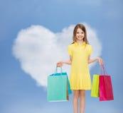 礼服的微笑的小女孩有购物袋的 免版税库存照片