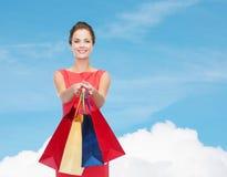 礼服的微笑的端庄的妇女有购物袋的 免版税图库摄影