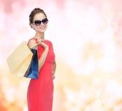礼服的微笑的端庄的妇女有购物袋的 库存图片