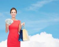 礼服的微笑的端庄的妇女有购物袋的 免版税库存照片