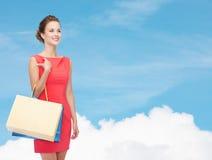 礼服的微笑的端庄的妇女有购物袋的 免版税库存图片